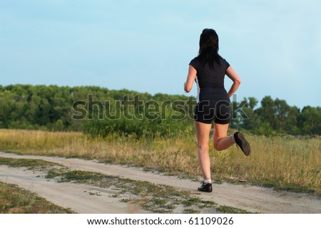 Woman jogging outdoors in summer meadow - stock photo