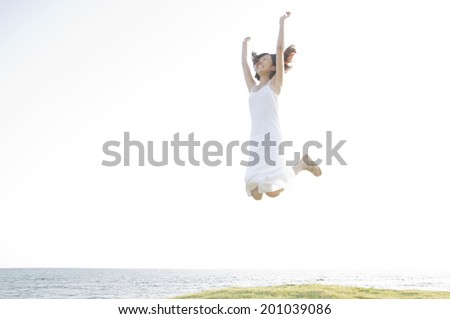Woman jumping at the seaside - stock photo