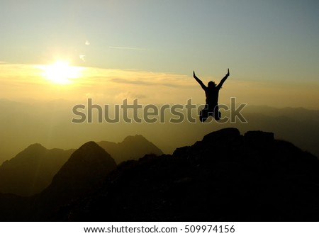 Woman jumping Hands up on the Top of the Nebelhorn Mountains in Germany Alps