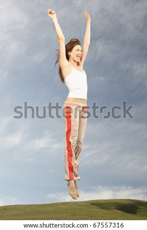 Woman jumping in air with hands over head
