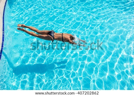 Woman jumping into the swimming pool. - stock photo
