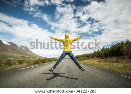 Woman jumping on a beautiful road  - stock photo