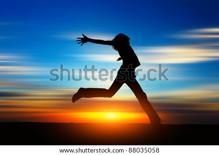 Woman jumping on a meadow at sunset with motion blurred clouds on the background - stock photo