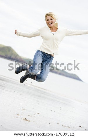 Woman jumping on beach smiling - stock photo