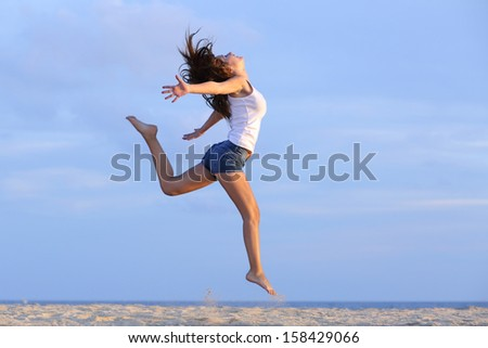 Woman jumping on the sand of the beach with the horizon in the background - stock photo