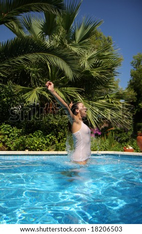 Woman jumping outside a pool with tropical palms in background - stock photo