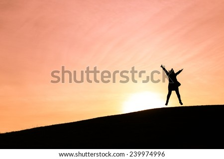 Woman jumping up in the air against a setting sun