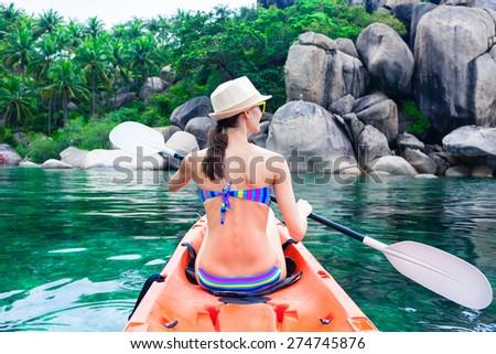 Woman kayaking in a beautiful island getaway.   - stock photo
