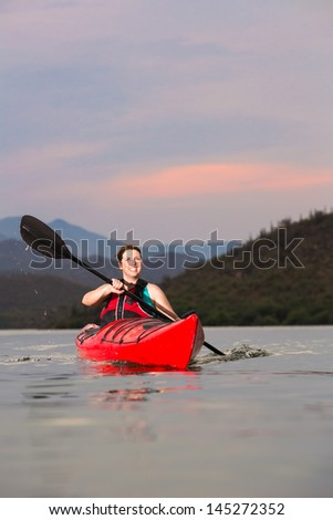 Woman Kayaking on Desert Lake - stock photo