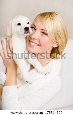 Woman keeping white puppy of Labrador near her face - stock photo