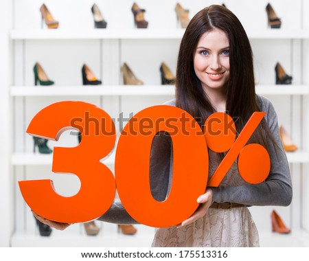 Woman keeps the model of 30% sale on footwear standing at the shopping center against the showcase with pumps - stock photo