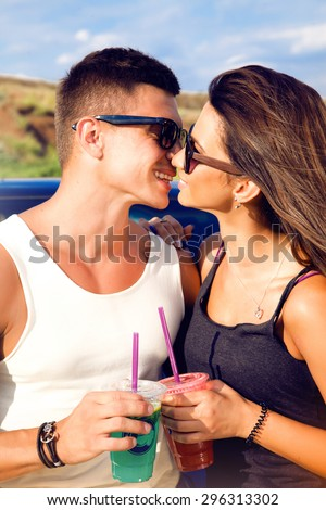 Woman kissing her boyfriend driving a car.Lovely young couple on road trip.Affectionate caucasian couple enjoying road trip,cocktail, smoozy drink, denim jacket,smiling,fashion,teen,cool accessories - stock photo