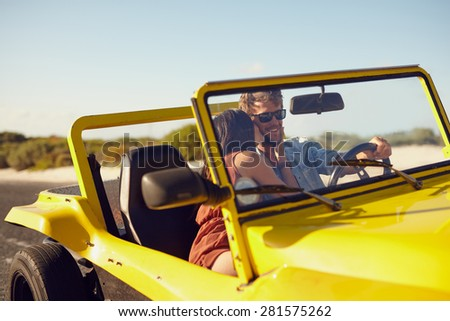 Woman kissing man driving car. Couple on road trip. Romantic caucasian couple on holiday having fun in car. - stock photo