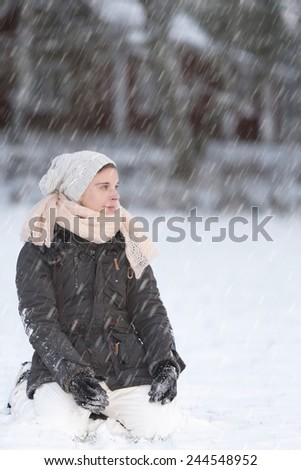 Woman kneeling in the snow and enjoy the fresh falling snow - stock photo