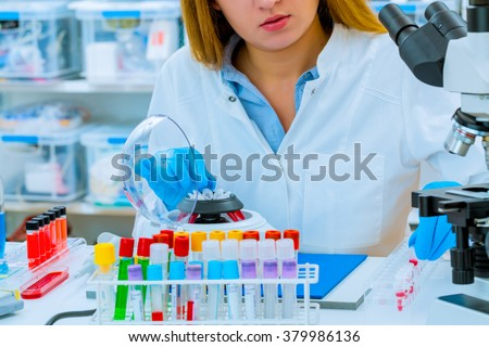 Woman laboratory assistant sets PCR test micro tubes in a centrifuge.  - stock photo