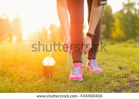 Woman lacing running shoes before workout. Fitness and healthy lifestyle concept.