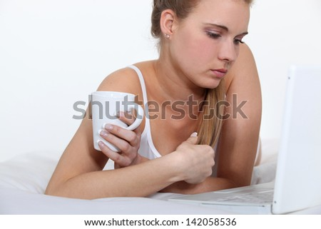 Woman laid on her bed using notebook - stock photo