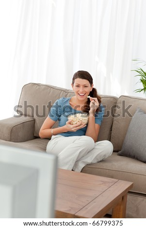Woman laughing while watching a movie on television in the living room at home - stock photo