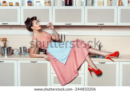Woman lay on the kitchen table and flirting eats cake. On her feet with a large red shoes heel. - stock photo