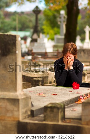 Woman Laying Flower on Grave in Cemetery - stock photo