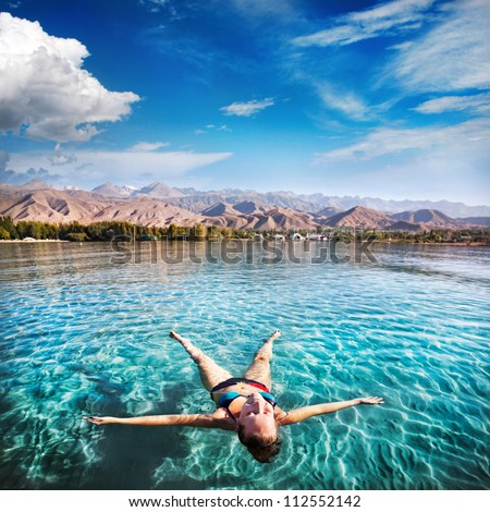 Woman laying like a star in Issyk Kul lake at mountains background in Kyrgyzstan, central Asia - stock photo