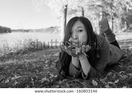 Woman laying on grass blowing away a handful of leaves