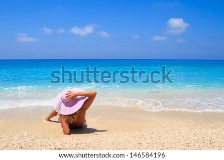 Woman laying on the beach in beach pink straw hat enjoying summer holidays looking at the ocean - stock photo