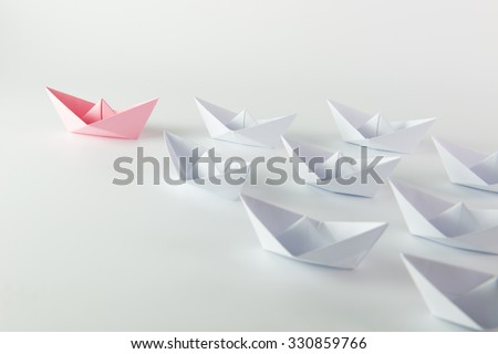 Woman leadership concept with pink paper ship leading among white