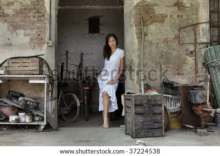 woman leaning against the door of garage - stock photo