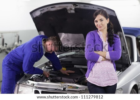 Woman leaning on a car next to a mechanic in a garage - stock photo