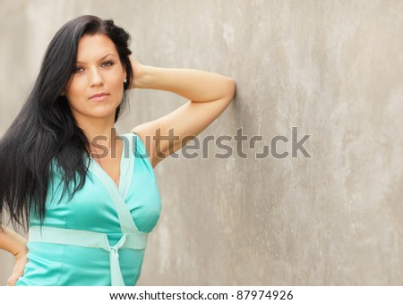 Woman leaning on a concrete wall