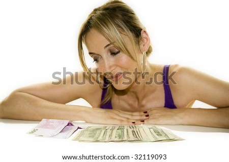 Woman leaning on a table looking at some cash - stock photo