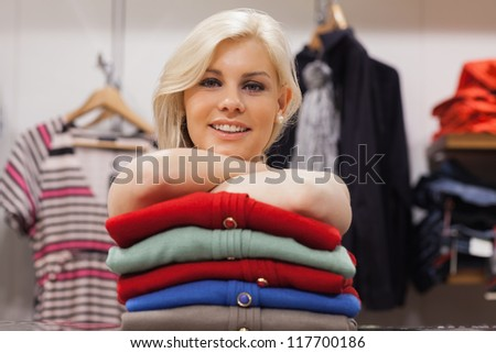 Woman leaning on clothes at a boutique smiling - stock photo