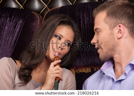 woman leaning on sofa and resting in Arabic cafe. man and woman smoking hookah and looking - stock photo
