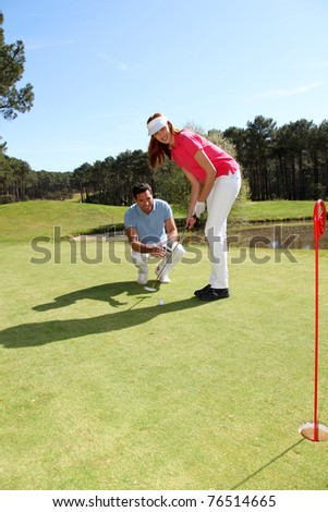Woman learning how to play golf - stock photo