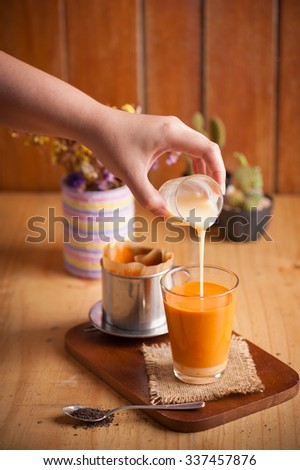 Woman left hand pouring fresh milk into glass of Dripped Thai tea by Vietnamese style on wood table in cafe - stock photo