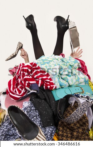 Woman legs and hands reaching out from a big pile of clothes and accessories.  Woman buried under an untidy cluttered wardrobe. Woman in high heels needs help from to much shopping. Shopaholic girl. - stock photo