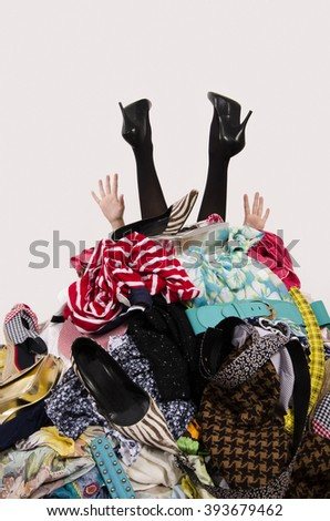 Woman legs and hands reaching out from a big pile of clothes.Woman buried under an untidy cluttered woman wardrobe. Woman in high heels needs help from to much shopping. Shopaholic girl. - stock photo