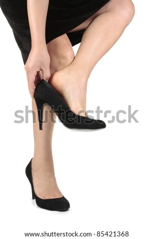 Woman legs black dress putting on heels  shoes over white