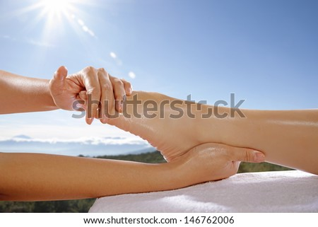Woman legs get foot massage with blue sky background. This is spa concept - stock photo