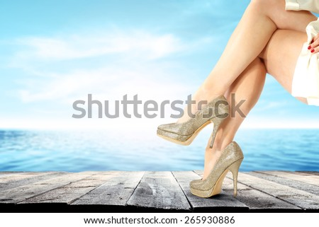 woman legs gold shoes and wooden old pier with blue sea