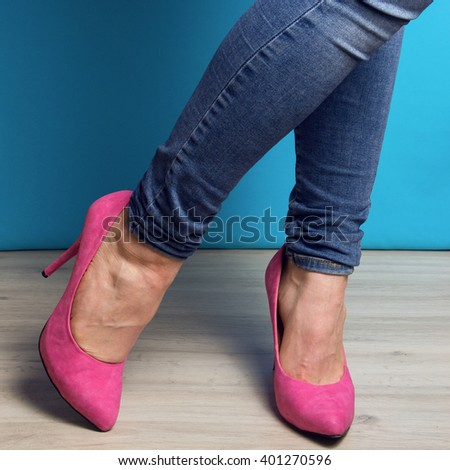woman legs in blue jeans and pink high heel shoes  blue background - stock photo
