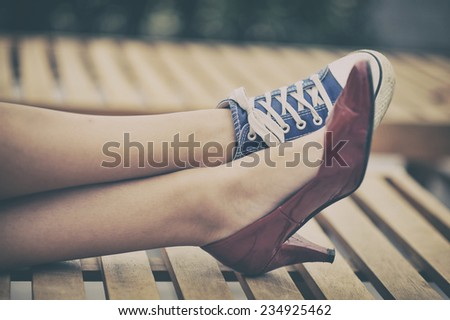 Woman legs in different shoes - stock photo