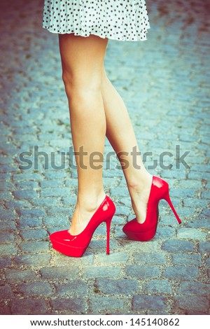 woman legs in red high heel shoes and short skirt outdoor shot on cobble street - stock photo