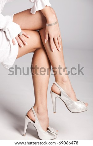 woman legs in silver high heels shoes, studio shot - stock photo