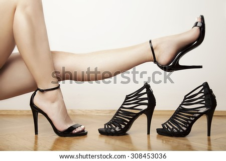 woman legs in stylish black heels, studio white - stock photo