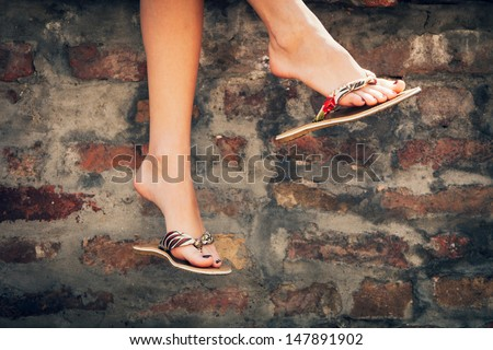 woman legs in  summer slippers outdoor day  shot  in the city - stock photo