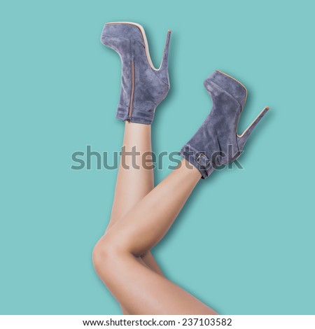 woman legs in velour high heel platform ankle boots lean on pastel blue wall upside down - stock photo