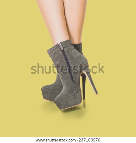 woman legs in velour high heel platform ankle boots on warm yellow background - stock photo