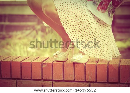 woman legs in white high heel shoes and short skirt outdoor shot on brick wall - stock photo
